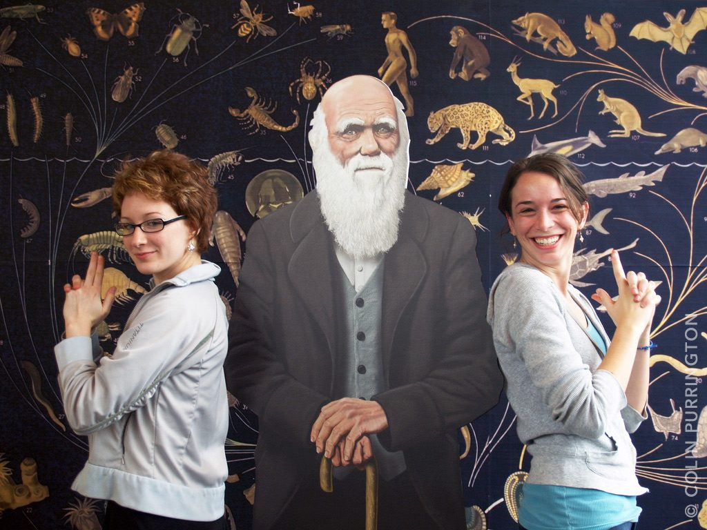 Charles Darwin posing with two angels