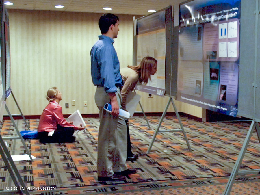 Viewers stooping to read conference poster in dimly-lit room